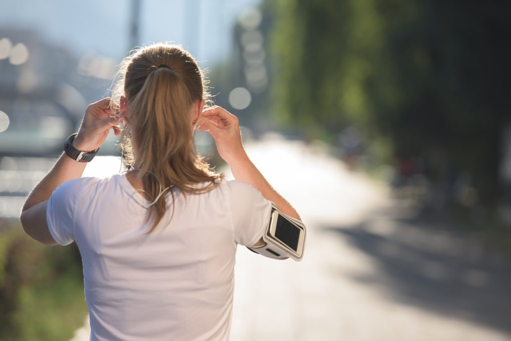 runner woman listening to podcast for morning run
